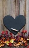 与秋叶、板岩心脏和白垩的背景 免版税库存照片