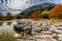 与秋叶的树在Frio河的一岩石河岸有小山的在背景中 免版税库存图片