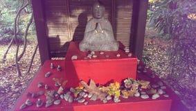 与秋叶的祈祷的修士雕象 免版税库存图片