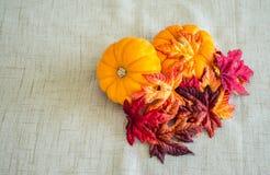 与秋叶的2个小南瓜在棕褐色的布料背景 免版税库存照片