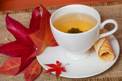 与秋天叶子和酥皮点心的红茶 免版税库存图片