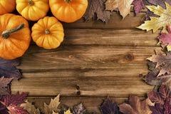 与秋天叶子的南瓜在木背景 顶视图 免版税库存图片