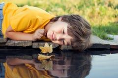 与秋天叶子船的男孩戏剧在水,孩子中在公园演奏w 免版税库存图片
