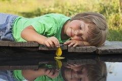 与秋天叶子船的男孩戏剧在水,孩子中在公园演奏w 免版税库存照片