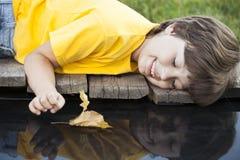 与秋天叶子船的男孩戏剧在水,孩子中在公园演奏w 库存照片