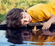 与秋天叶子船的男孩戏剧在水,孩子中在公园演奏w 图库摄影