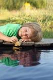 与秋天叶子船的男孩戏剧在水,孩子中在公园演奏wi 图库摄影