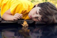 与秋天叶子船的男孩戏剧在水中, 库存图片