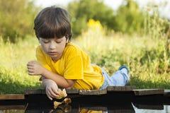 与秋天叶子船的男孩戏剧在水,孩子中在公园演奏wi 库存照片