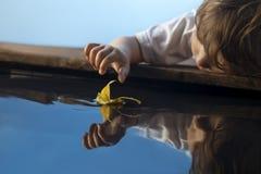 与秋天叶子船的男孩戏剧在水,孩子中在公园演奏wi 库存图片