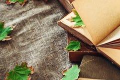 与秋天槭树的葡萄酒书在桌留下被放置的大袋 库存图片