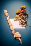 与秋天的白纸卡片开花束和丝带在减速火箭的蓝色背景 免版税库存图片