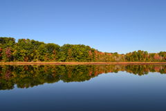 与秋天秋天颜色的美好的树反射在湖 库存图片
