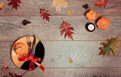 与秋天装饰的表设置 叉子,刀子,餐巾,利器,五颜六色的叶子 被点燃的背景电灯泡色的装饰诗歌选节假日光 感恩晚餐 免版税库存照片