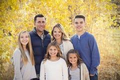 与秋天颜色的美丽的年轻家庭画象在背景中 库存图片