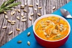 与种子、芝麻和迷迭香,顶视图的南瓜乳脂状的汤 库存照片