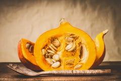 与种子和木烹调匙子的半南瓜在自然米黄背景,正面图 健康秋天季节性食物 免版税库存照片