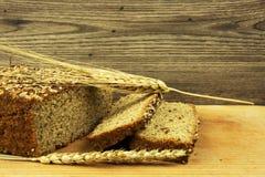 与种子和谷物钉的面包在木背景 免版税库存图片