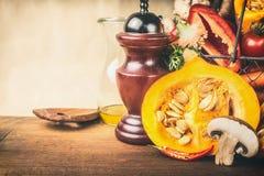 与种子的半南瓜和在木厨房用桌,正面图上的其他素食成份 健康秋天季节性烹调 免版税库存照片