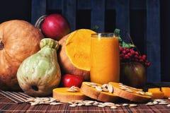 与种子的可口新鲜的南瓜汁在木背景的演播室 库存图片