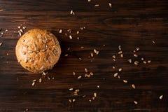 与种子的小圆面包在黑暗的木背景 免版税库存照片