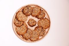 与种子的特写镜头自创自然燕麦粥饮食精瘦的曲奇饼在白色背景隔绝的一块圆的木板材 ?treadled 免版税库存图片