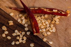 与种子的红色干辣椒在砧板 库存图片