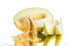 与种子的黄色切的瓜在被隔绝的白色镜子背景紧密  免版税库存照片