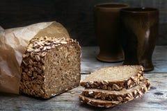 与种子的整粒面包在被风化的木头,黑暗的背景 库存照片