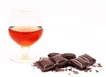 与科涅克白兰地和在白色隔绝的巧克力块堆的玻璃 库存图片