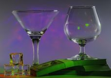 与科涅克白兰地玻璃一起的马蒂尼鸡尾酒玻璃在一盒100s美元和冰块与闪动的光滑的紫罗兰色光  库存照片