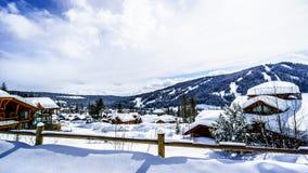 与积雪的屋顶的冬天风景在太阳峰顶高山村庄  免版税库存照片