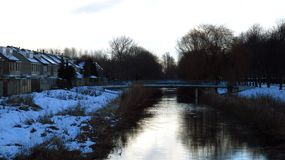 与积雪的桥梁和运河的冬天风景 免版税库存图片