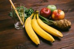 与秸杆、香蕉、芹菜根和苹果的空的玻璃在d 库存图片