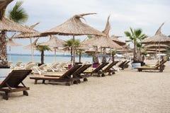 与秸杆伞和太阳懒人的海滩睡椅地区 balchik黑色保加利亚海岸海运城镇 节假日概念 库存图片