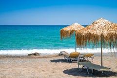 与秸杆伞和sunbeds,克利特,希腊的空的海滩 免版税库存图片