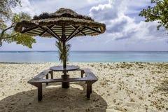 与秸杆伞的野餐桌在热带海滩 库存图片