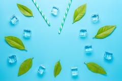 与秸杆和冰块的创造性的夏天构成在蓝色背景 最小的饮料概念 免版税图库摄影