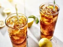 与秸杆和柠檬切片的冷的被冰的茶在夏天星期日。 免版税库存照片