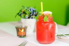 与秸杆的新鲜的西瓜汁在瓶子,水平 免版税图库摄影