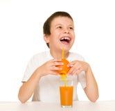 与秸杆的男孩饮料橙汁 库存图片