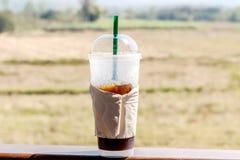 与秸杆的被冰的咖啡在一张木桌上的塑料杯子在summe 图库摄影