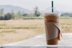 与秸杆的被冰的咖啡在一张木桌上的塑料杯子在summe 免版税库存照片