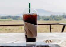 与秸杆的被冰的咖啡在一张木桌上的塑料杯子在summe 库存图片