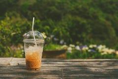 与秸杆的被冰的牛奶茶在塑料杯子 免版税库存图片