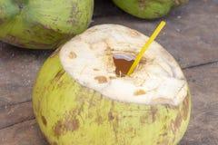 与秸杆的被打开的椰子准备好喝 新鲜的椰树水照片 在木桌上的椰子果子 图库摄影
