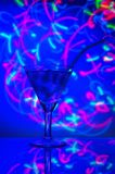 与秸杆鸡尾酒的玻璃与反对抽象照明背景的冰  免版税库存照片