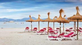 与秸杆sunbeds和遮阳伞的海滩  库存图片