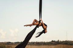 与空中丝绸的高雅年轻美好的妇女舞蹈在天空背景 飞行瑜伽体育 库存照片