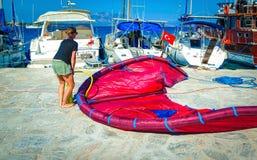 与空气的Kitesurfer妇女抽的积土她的风筝 免版税库存图片